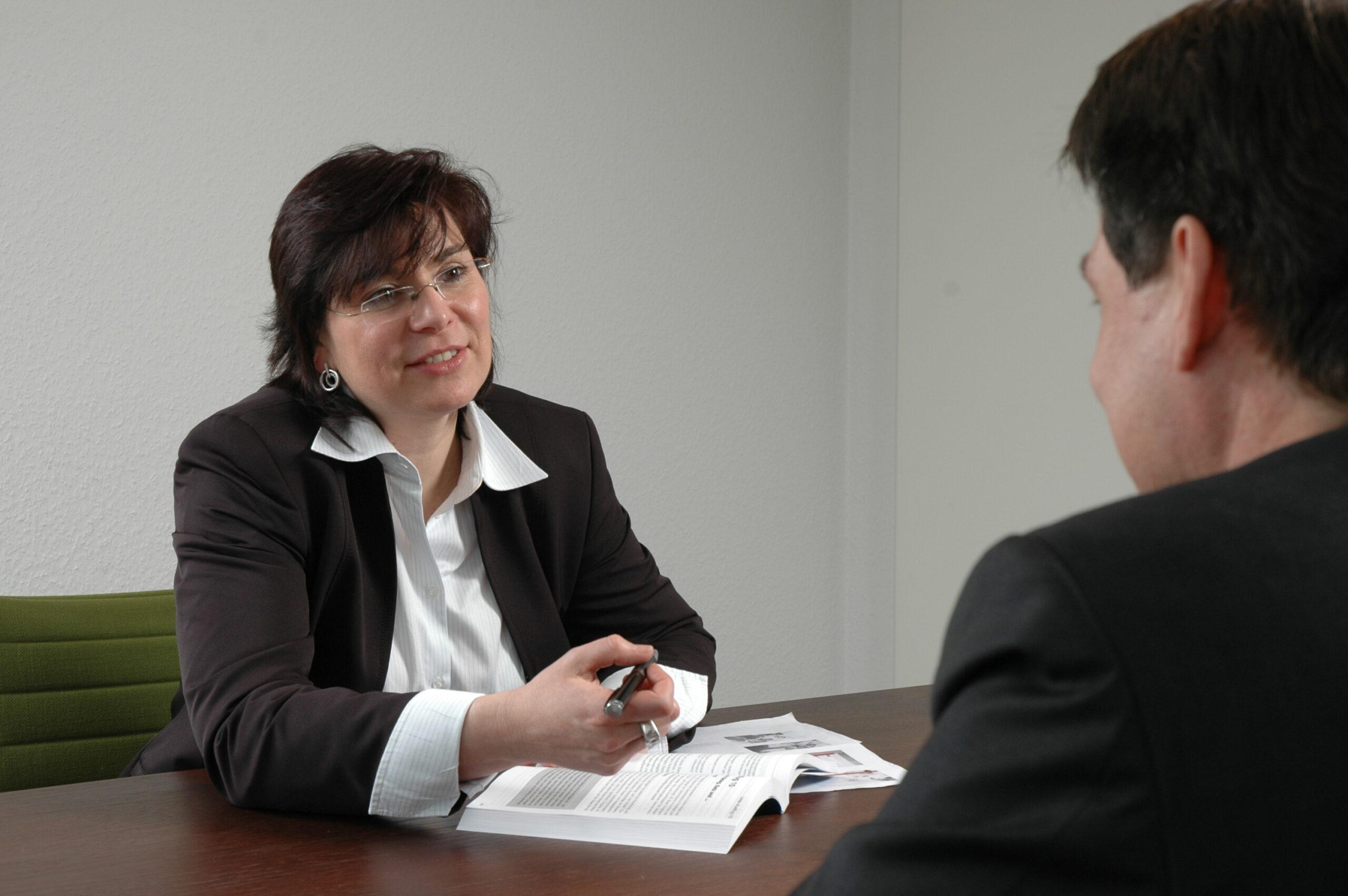 Frau Bangert berät einen Kunden im Einzelgespräch