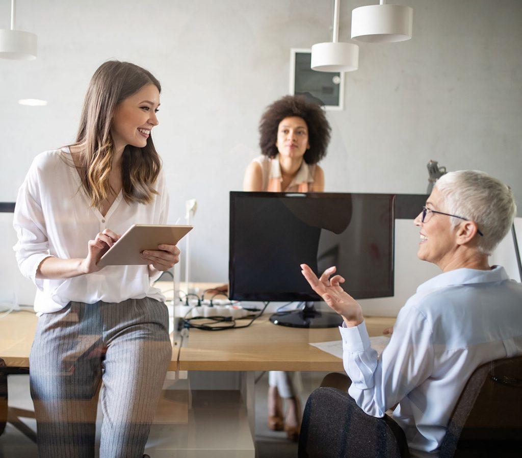 Drei Kolleginnen unterhalten sich lächelnd im Büro