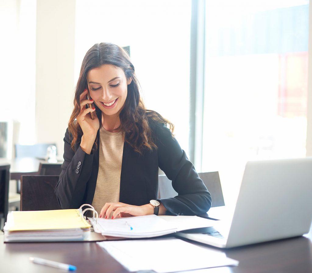 Business-Frau telefoniert am Schreibtisch sitzend